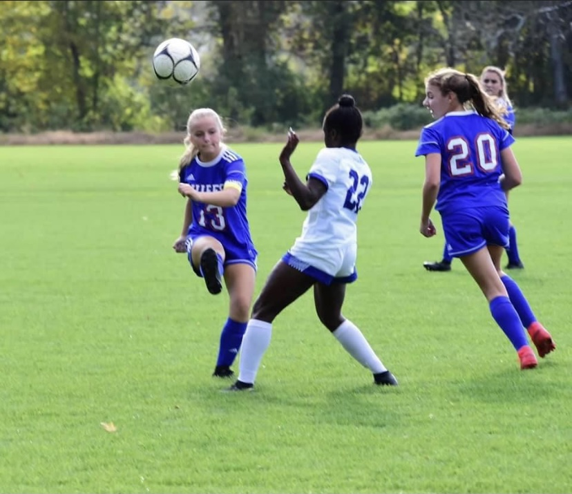 Mia Higgins (#13) kicking the ball past the defender with Mallory Tomkalski (#20) and Reilly Faraci (in the back) playing defense