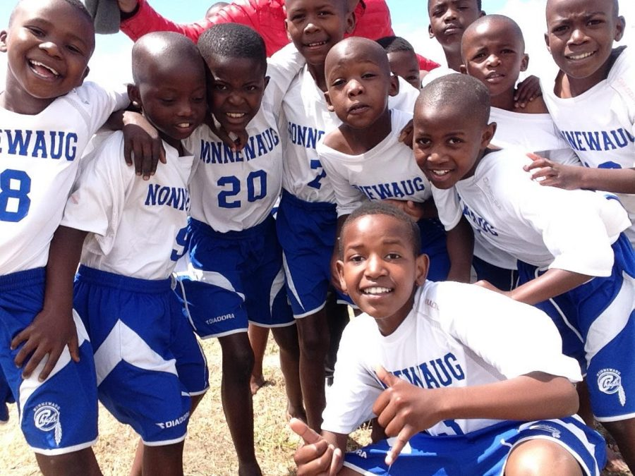 Young athletes from Khayelitsha Township in Cape Town, South Africa celebrate the arrival of their new uniforms, donated by Nonnewaug's athletic department.