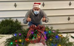 Eric Birkenberger shows his approval after finishing the decorations for one of the wreaths sold at the Woodbury FFA holiday plant sale.