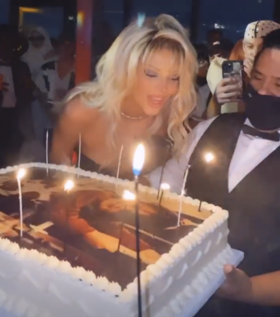 Kendall Jenner blows out her birthday cake candles while a masked waiter holds the cake at an Oct. 31 party. Jenner is among the celebrities who received backlash for partying during the COVID-19 pandemic.