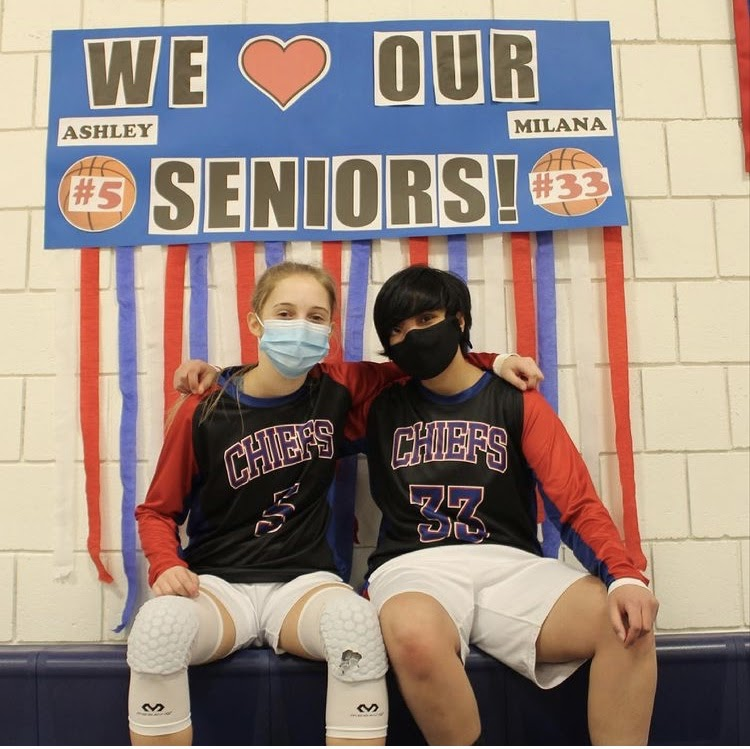 Seniors Ashley Henessey (#5) and Milana Jaffin (#33) gather in front of one of their many senior night posters.