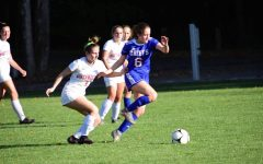 NHS student-athlete Marley Baker is defending the Chiefs' goal as a forward from Northwest challenges her.